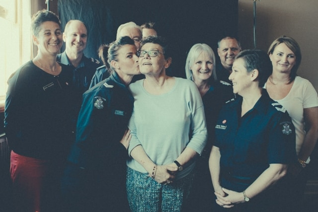 Eddie lives with early onset dementia. She stands in the middle of a group of plain clothes and uniformed police. The female police officer to her right is kissing Eddie on her cheek.