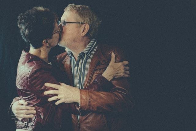 Christine lives with dementia. She wears a red leather jacket. Paul wears a tan leather jacket. They are senior aged and they a lost in a kiss.