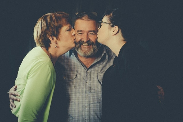 A man stands in the centre smiling as his wife and daughter kiss him on the cheeks
