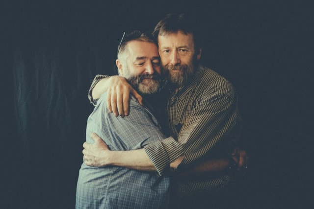 Two middle aged men embrace. Kieran who lives with Alzheimer's stands to the left of Joff.