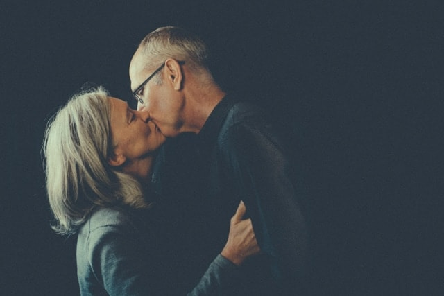 A grey haired Jane kisses her husband. Rob lives with dementia