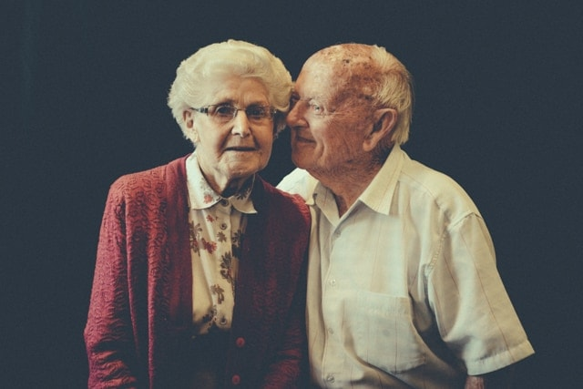 An elderly woman with grey hair and glasses leans into her husband as he kisses her on the cheek