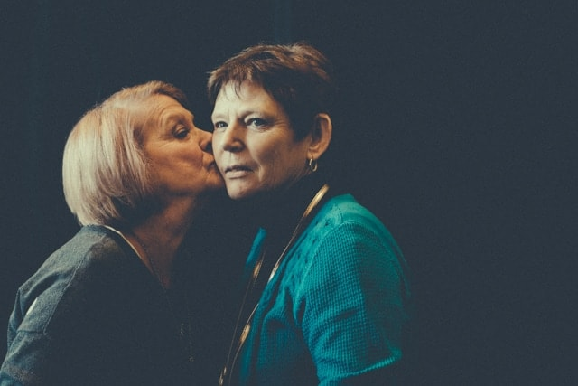 Glenda kisses Brenda on the cheek. Brenda gazes off into the distance. Brenda lives with dementia