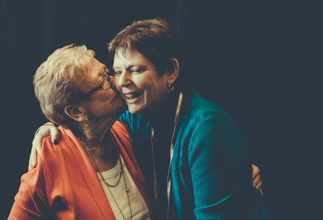 An 80 year old mother kisses her middle aged daughter on the cheek. The daughter lives with dementia