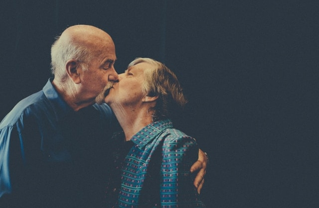 An older balding man embraces and kisses his wife. His wife is wearing a blue formal dress.