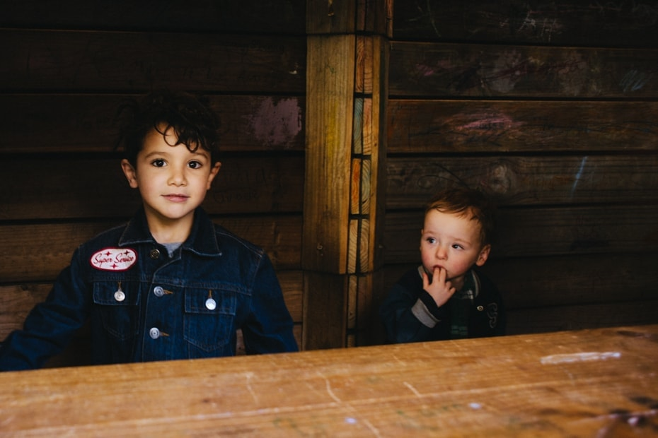 Two small children look out from their hut. Part of the childrens play area at the venue of the birthday party
