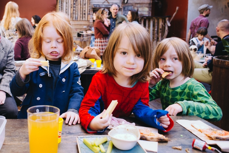 Three young boys eat pizza and drink cordial at the birthday party.