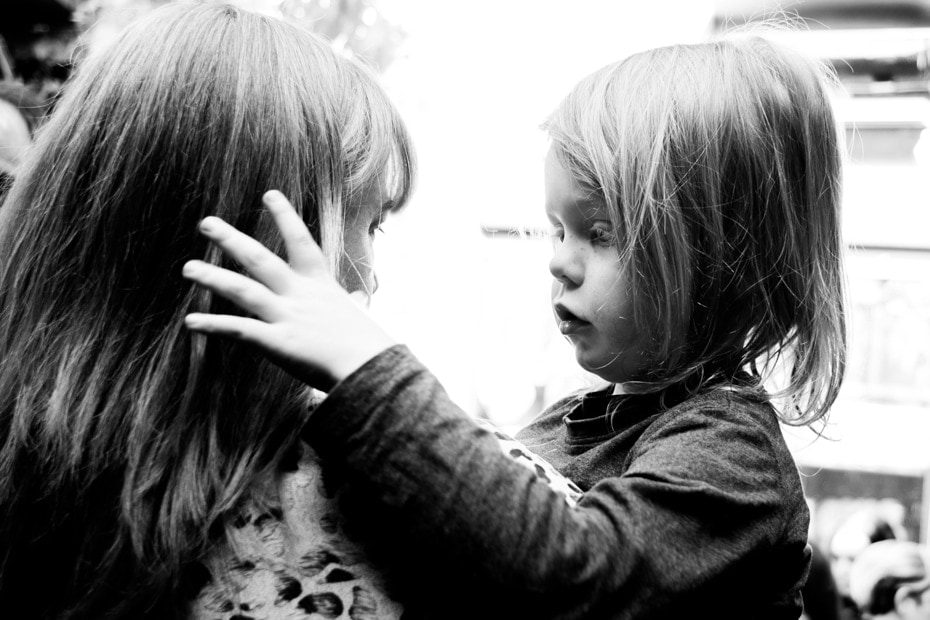 A young child touches his mothers hair as she consoles him.