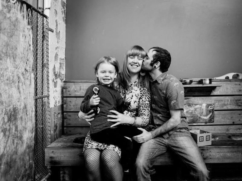 The birthday girl, her partner and son pose for a family portrait. Her partner kisses her on the cheek.