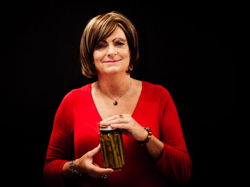 An older transgender woman wearing a red sweater holds a jar of preserved asparagus
