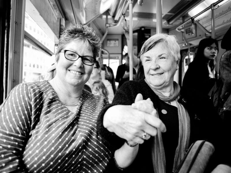 A close up of two women holding hands on a tram