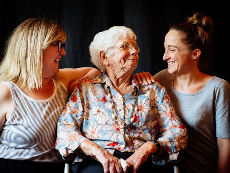 An elderly woman, sitting in a wheelchair is surrounded by her two Grand-Daughters.