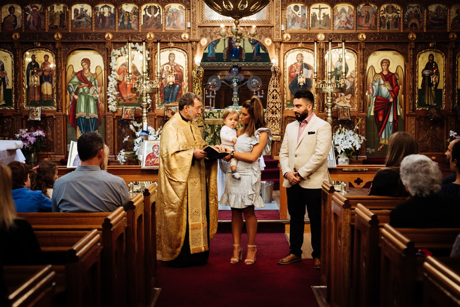 A Greek Orthodox Priest introduces the baptised infant to the congregation. The God-Mother holds the infant, while the God-Father looks on