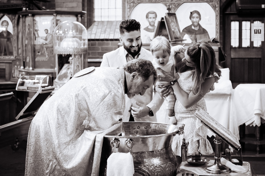 A Greek Orthodox Priest, tests the baptism water temperature. The God-Parents and infant look on
