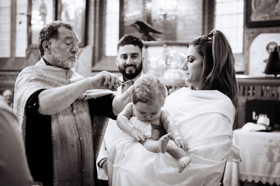 A Greek Orthodox Priest, cuts the hair of the baptised infant. The God-Parents look on.