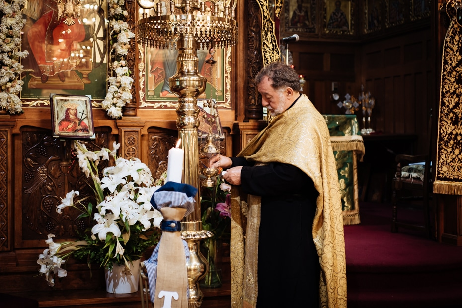 A Greek Orthodox Priest prepares the incense burner at a christening. The setting is an ornate Greek Orthodox Church with lots of gold trimings and images of Saints