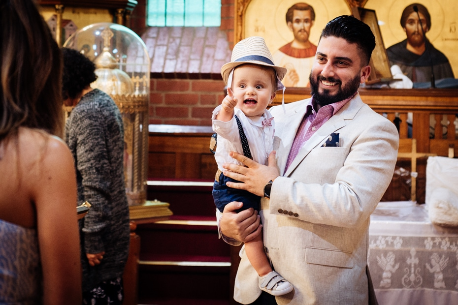 A young bearded man wearing a white jacket, holds his Godson. The infant is wearing a hat and is smiling and pointing at his God-Mother