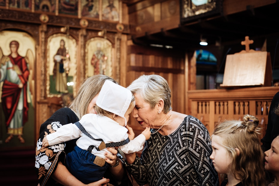 A mother holds her baptised son while an elderly woman kisses the infant. He is wearing his baptism bonnet