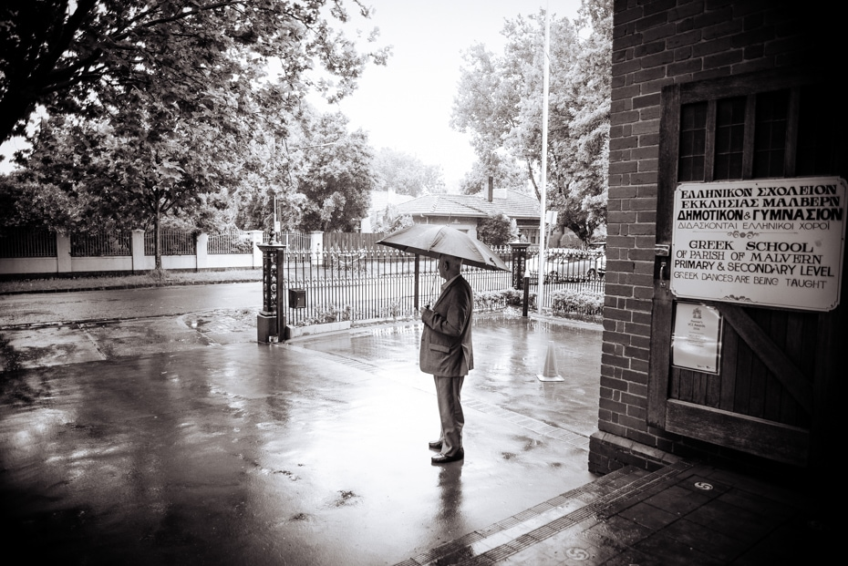 A man carrying an umbrella stands in the rain outside a church, waiting to welcome guests