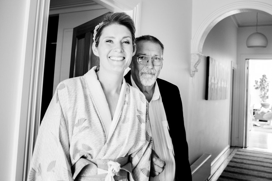 A Bride dressed in a dressing gown stands with her father in the hallway. Both are smiling.