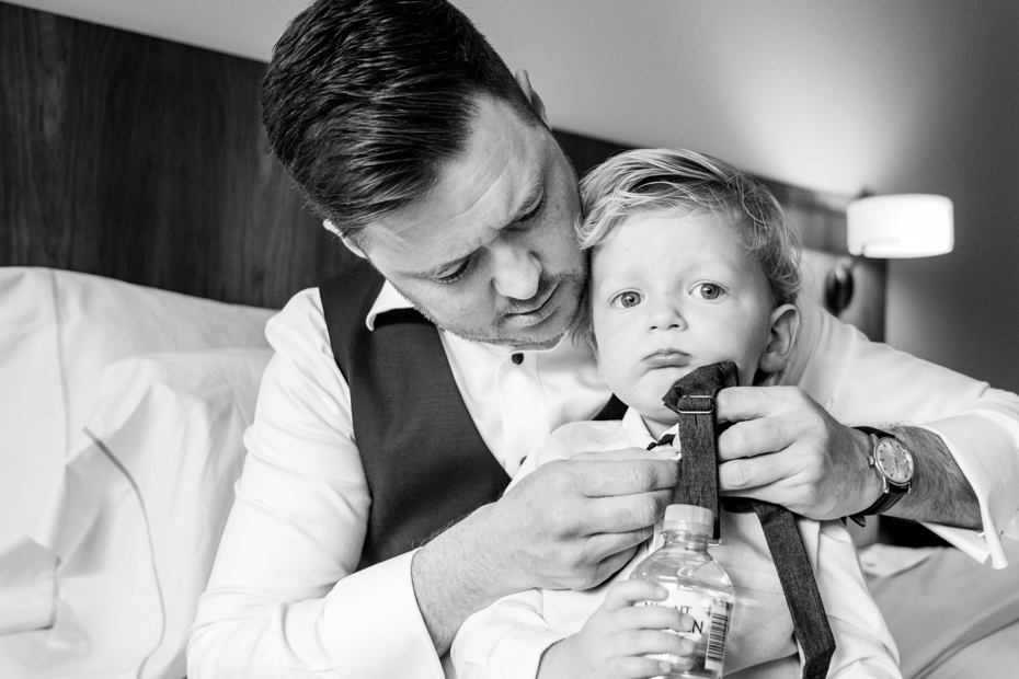 A father, sitting on his bed fixes his young son's tie.