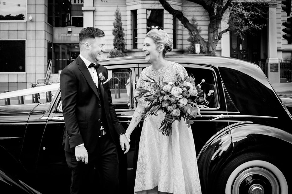 A Bride and Groom standing beside their bridal car. She is carrying a large bouquet of flowers. Both are smiling.