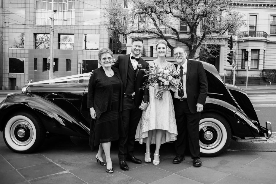 A group shot of the Bride and Groom with the bride's family standing beside the black bridal car.