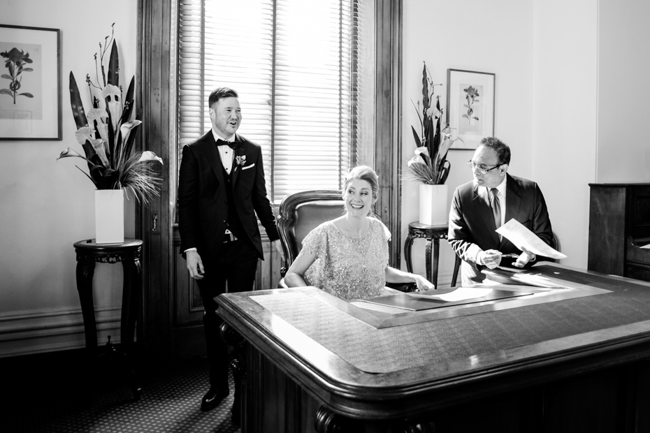 A shot of the Bride sitting at a large desk, signing the wedding registry. The Groom and celebrant look on.