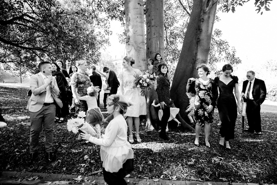 A large group shot of the wedding guests under a Morton Bay Fig tree. The Bride stands in the midst.