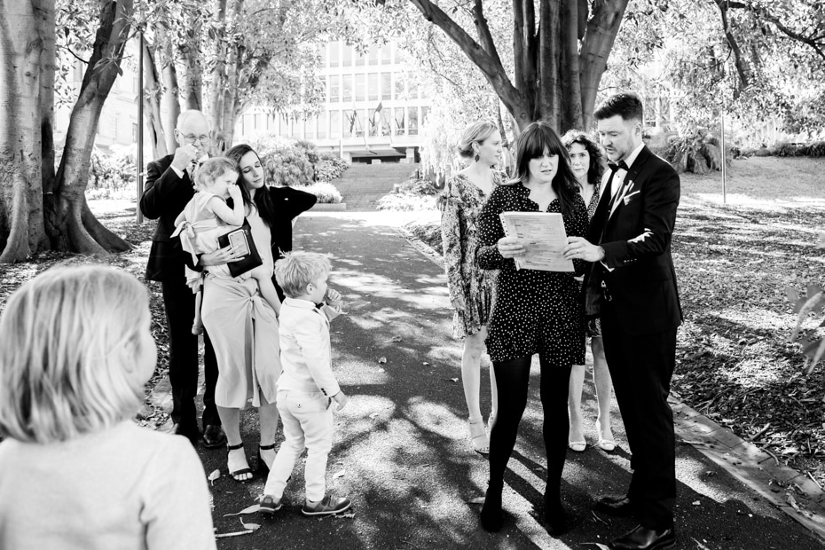 Under the shade of Morton Bay Fig trees, the Groom and his sister check the list for the formal bridal shots.