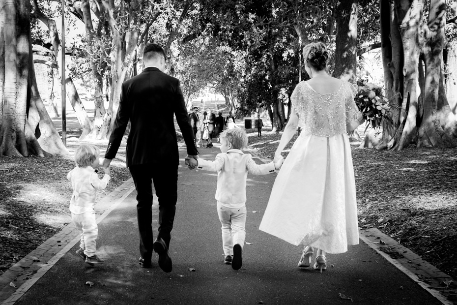 The Bride and Groom walk hand in hand with their children through the Morton Bay Fig tree avenue at Treasury Gardens, Melbourne.