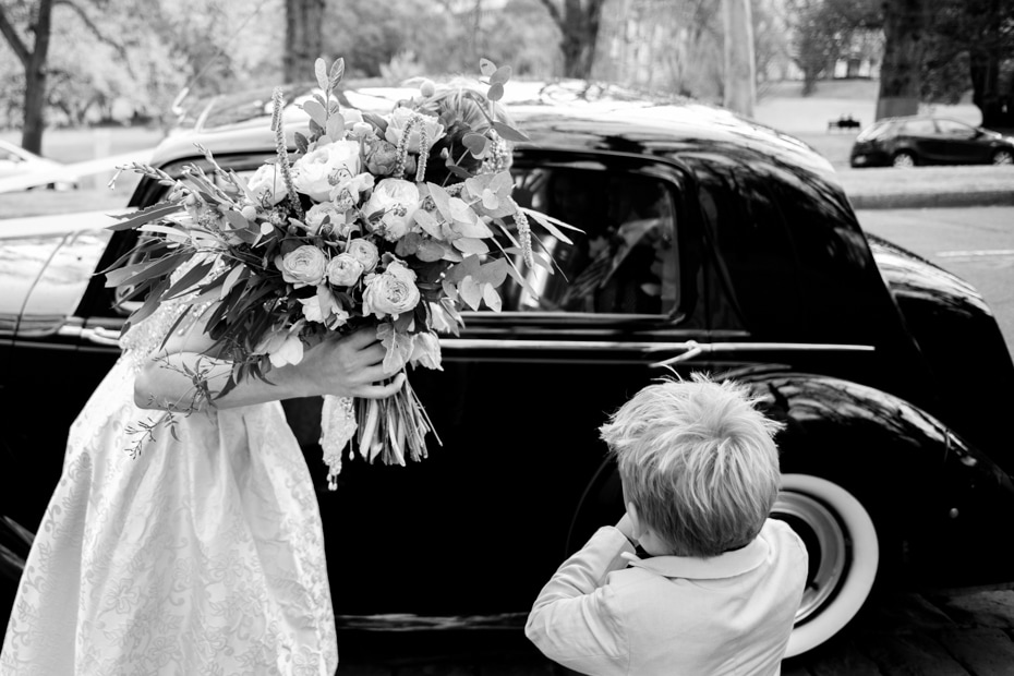 The Bride with her face obscured by her large bouquet of flowers leans towards her parents in the bridal car. Her young son looks on, sucking his thumb.