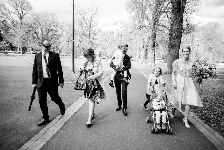 The Bride and Grooms family walk through the park.