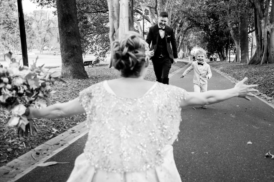 The Bride squatting with arms open, faces her husband as he and their young son run towards her.