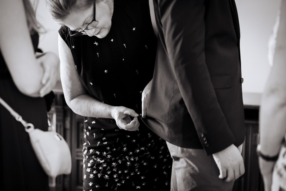 A mother does last minute mend on Grooms jacket.