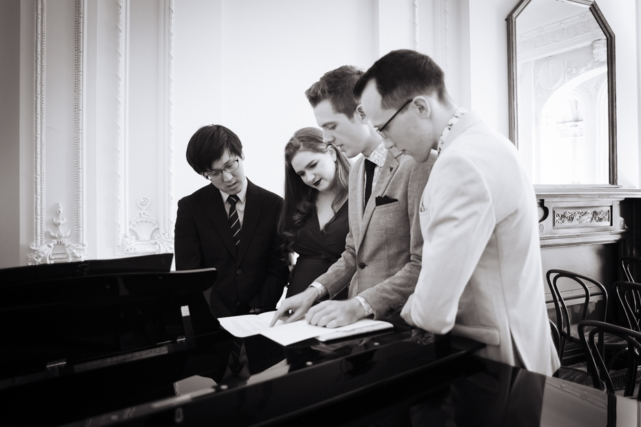 The grooms look over the music manuscript with the singer and pianist