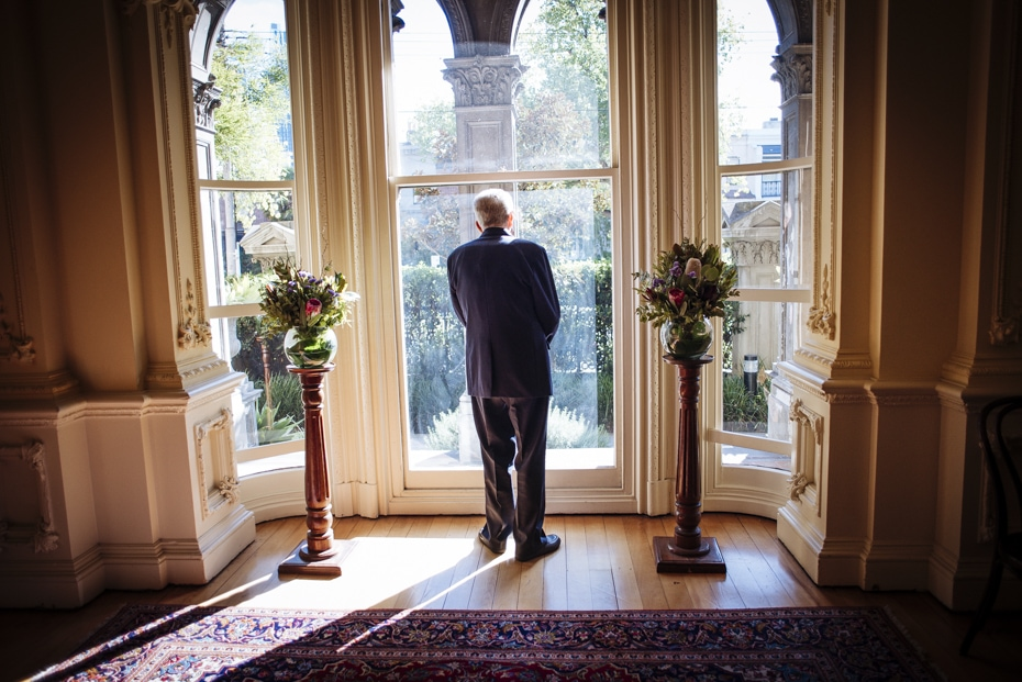 An elderly man gases into the garden and is silhouetted against the arched windows