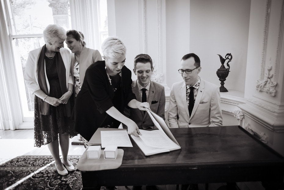 Celebrant indicates where the Grooms are to sign the wedding certificate. The two mother-in-laws are chatting and smiling in the background.