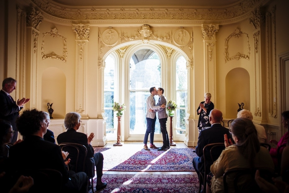 The Grooms first kiss as Husband and Husband. They are silhouetted against the arched window and the wedding party looks on and claps