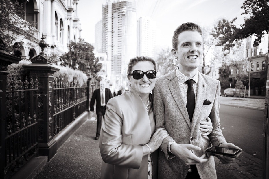 A very proud mum walks arm in arm up the street with her newly wed son. She is wearing large sunglasses and they are both smiling.