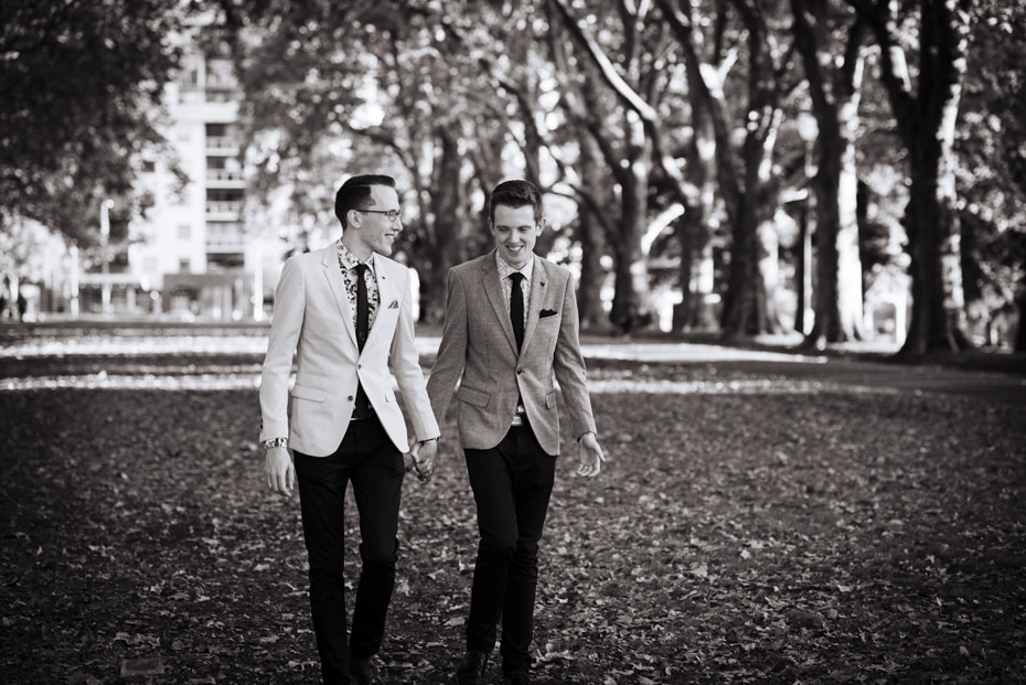 The two grooms walk hand in hand along a tree lined path in Exhibition Gardens, Melbourne.