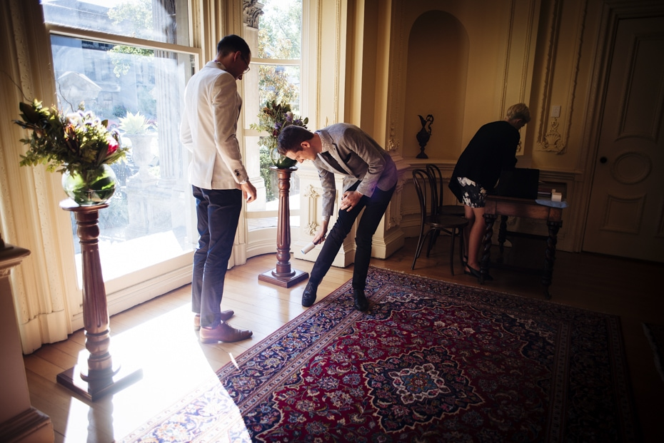 One groom looks on as the other groom removes lint from his trousers with a lint brush.