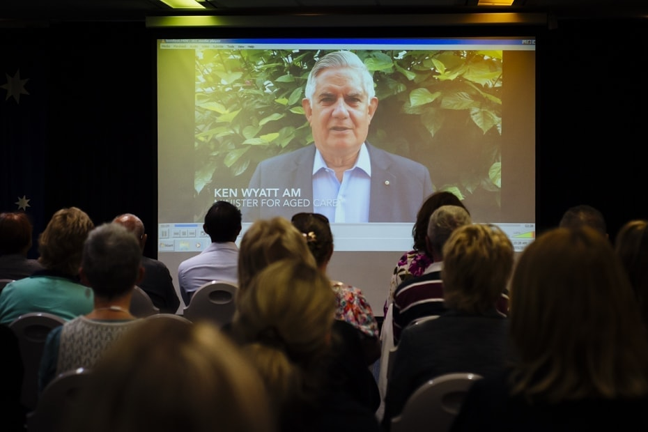 A crowd looks on a projected image of the minister of ageing Ken Wyatt AM, delivering an address