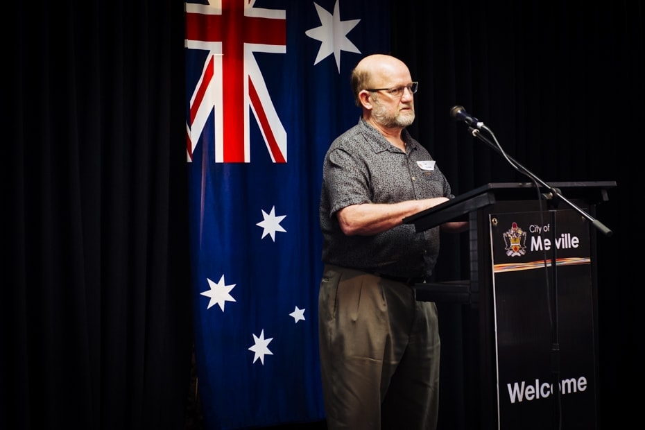 A middle balding aged man stands at a podium. The Australian flag hangs behind him