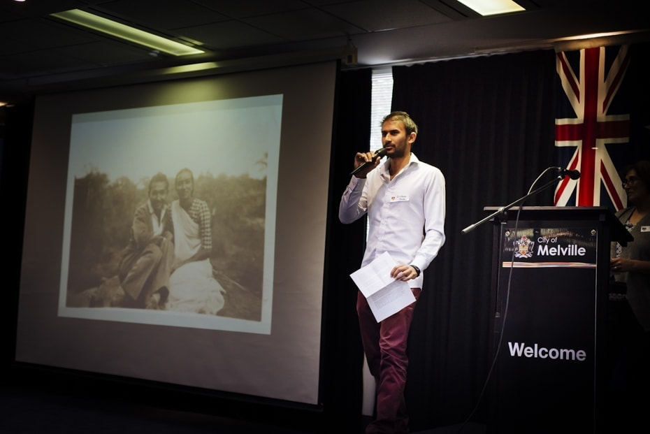 A young Indian man addresses the audience. A picture of his grandparents is projected on the screen beside him
