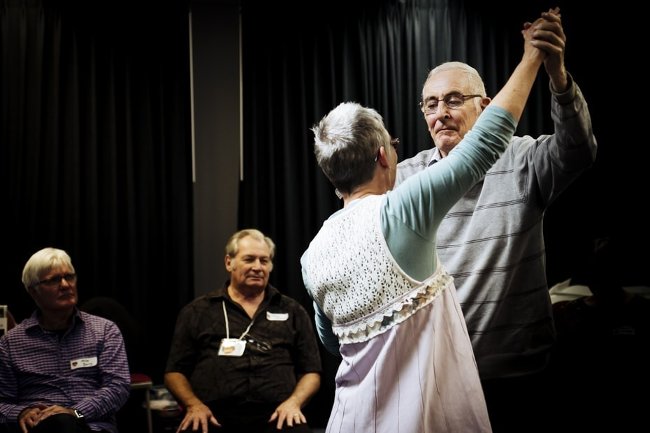 An older man dances with his dance instructor.