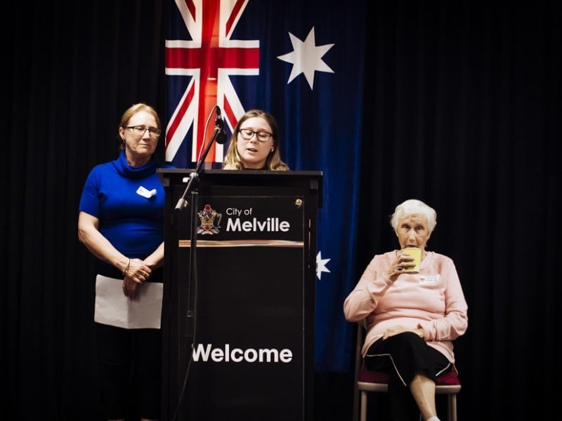 A granddaughter delivers her speech on the podium as her mother looks on and her Grandmother sits sipping tea