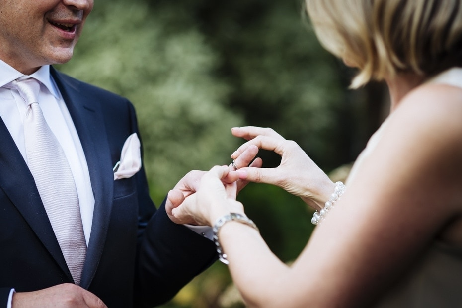 Bride places the wedding ring on her husbands hand during their wedding in the Royal Botanical Gardens, Melbourne